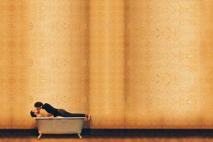 A woman kissing a man in a bath
